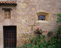Monterey County, CA:  In the courtyard a stonewall with summer garden and wood door leads to the Basilica at Carmel Mission Basilica (1797)