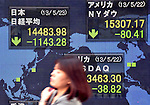 May 23, 2013, Tokyo, Japan - Oblivious to a record drop in share prices on the Tokyo Stock Exchange market, a passerby walks past the stock price board of a local brokerage in Tokyo on Thursday, May 23, 2013.The Nikkei share average plunged 7.3 per cent, its biggest one-day percentage drop in 13 years, ending at 14,483.98 in the 11th-largest point drop on record.  (Photo by Natsuki Sakai/AFLO)