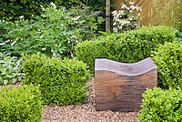 Buxus boxwood shrubs and wooden garden seat bench, with white bleeding heart perennial flowers, azaleas, Stachys, wall, in pretty spring garden scene in green and white color theme