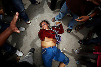 An election committee official lies unconscious after angry mob surrender her in protest against alleged election irregularities at a polling station in Phnom Penh July 28, 2013. Cambodians voted on Sunday in an election likely to hand another five years in power to Asia's longest-serving prime minister, Hun Sen, but an energised opposition says there have been irregularities and it will continue to fight for true democracy.  REUTERS/Damir Sagolj (CAMBODIA)