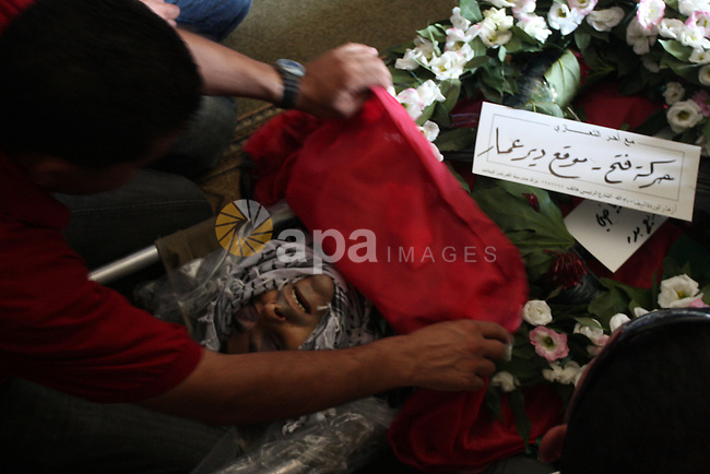 Palestinian mourners over the body of Akram Badr, 46, during a funeral in the village of Beitillu near in the West Bank city of Ramallah, Tuesday, July 31, 2012. Badr was killed at a checkpoint by the Israeli security forces near Jerusalem Monday. Photo by Issam Rimawi