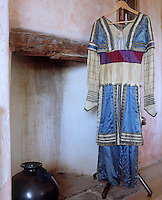 """A blue and white silk costume embellished with fabric covered silver buttons and bands of ribbons designed for the Ballet """"Thamar"""" in 1912"""