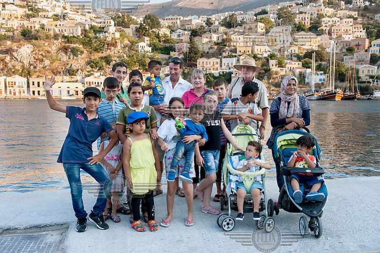Hotelier Andrew Davies and other British volunteers at he port of Symi together with a group of Refugees. Davies, a British ex-pat, helped found Solidarity Symi which helps refugees arriving from Turkey.