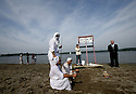 The priest, the groom, and a religious witness say some prayers while family members hang around the beach at Kensington Metro Park druing different phases of the rather lengthy Mandean ritual baptisms.