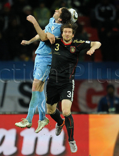 Diego Godin (L) of Uruguay challenges with Arne Friedrich of Germany during the 2010 FIFA World Cup third place match between Uruguay and Germany at the Nelson Mandela Bay Stadium in Port Elizabeth, South Africa 10 July 2010.