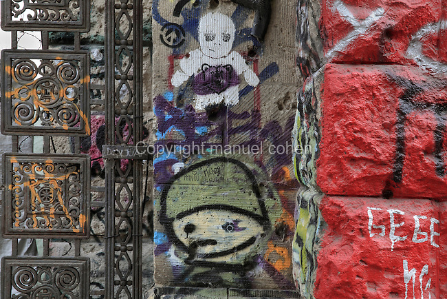 Graffiti on the walls and gates of the Kunsthaus Tacheles, an art centre established in 1990 containing artists' studios, workshops, a nightclub and cinema, which was closed down in 2012 and is now derelict, Oranienburger Strasse, Mitte, Berlin, Germany. The building was originally a department store built 1907-8 in the Jewish quarter or Scheunenviertel. Picture by Manuel Cohen