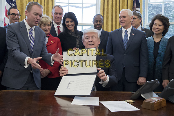 US President Donald J. Trump (C) shows an executive order entitled, 'Comprehensive Plan for Reorganizing the Executive Branch', after signing it beside members of his Cabinet in the Oval Office of the White House in Washington, DC, USA, 13 March 2017. Also in the picture is Director of the Office of Management and Budget (OMB) Mick Mulvaney (Front L),  Treasury Secretary Steven Mnuchin (Back L), Administrator of the Small Business Administration Linda McMahon (2-L), Secretary of the Interior Ryan Zinke (3-L), US Ambassador to the UN Nikki Haley (4-L), Secretary of Housing and Urban Developement (HUD) Ben Carson (Back C), US Vice President Mike Pence (2-R) and Secretary of Transportation Elaine Chao (R).<br /> CAP/MPI/RS<br /> &copy;RS/MPI/Capital Pictures