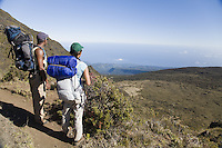Asian-American woman and African-American man with backpacks and sleeping bags, taking a break while hiking out of the Haleakala Crater on the Halemaumau Trail