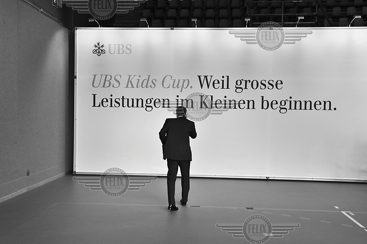 A man attending the annual general meeting of UBS, Switzerland's biggest bank, talks on  a mobile phone. There was a shareholder's revolt over the conduct of the bank's previous administration, which attendees regarded as responsible for record losses for a Swiss company, following exposure to the US sub-prime market and also a major investigation in the US into organised tax evasion that has called into question the whole concept of Switzerland's hallowed banking secrecy. Furthermore, a new scandal emerged in September 2011 when a rogue trader based in London was discovered to have lost in the region of USD 2.3 billion in unauthorised trading. In response Oswald Grubel, Group Chief Executive Officer at UBS, resigned.