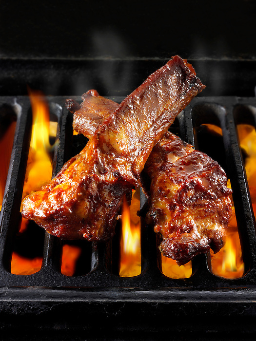 BBQ spare ribs being cooked over open flames. Food bbq photos, pictures & images.