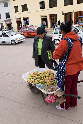 A CUZCO PERU STREET VENDOR USES HER WHEELBARROW AS A VEGETABLE STAND
