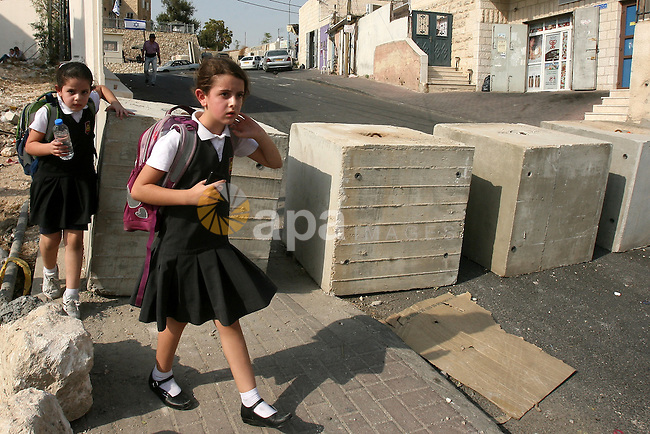 Palestinian school girls walk between cement blocks at a newly erected checkpoint in Jerusalem's neighborhood of Jabal al-Mokaber on October 19, 2015. Israeli police began erecting a wall in east Jerusalem to protect a Jewish neighbourhood subject to firebomb and stone attacks launched from an adjacent Palestinian village. Photo by Mahfouz Abu Turk