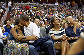 "July 16, 2012.""The President and First Lady were attending the game between the United States Men's Olympic basketball President Barack Obama and Brazil in Washington, D.C. During the first half, the jumbotron flashed couples on their 'Kiss Cam', where they are then induced by the crowd to kiss each other. But neither the President or First Lady saw themselves when they were flashed on 'Kiss Cam', and some in the audience booed when they didn't kiss. At halftime, as we walked to the locker room to visit the U.S. team, daughters Malia and Sasha were asking their parents why they hadn't kissed during their 'Kiss Cam' moment. Both the President and First Lady said they hadn't even realized what had happened and didn't know why people were booing. So in the second half, when they appeared again on the 'Kiss Cam', the President leaned over to kiss the First Lady amongst audience cheers as Malia and the Vice President watched overhead on the jumbotron."" .Mandatory Credit: Pete Souza - White House via CNP"