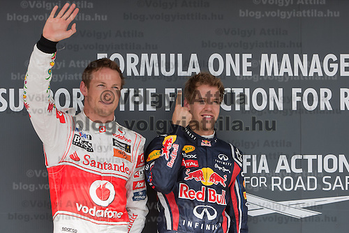 McLaren Formula One driver Jenson Button (L) of Britain and Red Bull Racing Formula One driver Sebastian Vettel (R) of Germany celebrate their victory during the qualifyer of the Hungarian F1 Grand Prix in Mogyorod (about 20km north-east from Budapest), Hungary. Saturday, 30. July 2011. ATTILA VOLGYI