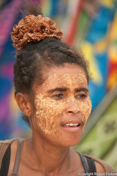 Young woman selling gifts at beach, Ifaty, Madagascar with face paste to protect from the sun and as a beautification