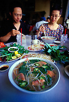 Asian couple enjoying bowls of Pho, a traditional Vietnamese noodle soup with sliced beef, chili peppers, bean sprouts, and Thai basil, at To-Chau Restaurant, River St., Chinatown, Honolulu