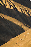 Shadows define the gullies and patterns of the bare hillside in the foothills of the Panamint Mountains at the mouth of Surprise Canyon, Calif.