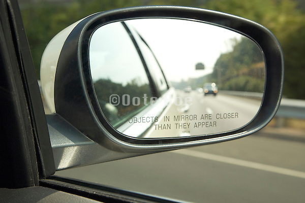 warning text concerning distance in the outside side mirror of a car