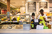 Miaamour McCants, right, trains new employee Alex Hufford on the cash register at the newly-opened Cafe Symmetry in Carrboro, North Carolina.