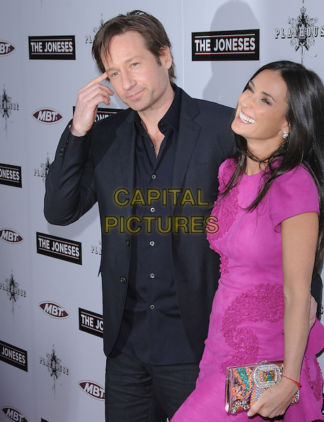 "DAVID DUCHOVNY & DEMI MOORE .at the L.A. Premiere of ""The Joneses"" held at The Arclight Theatre in Hollywood, California, USA, .April 8th, 2010..arrivals half length hand finger smiling touching face suit jacket pink purple dress clutch bag red string kabbalah bracelet grey gray black shirt                                                         .CAP/RKE/DVS.©DVS/RockinExposures/Capital Pictures."