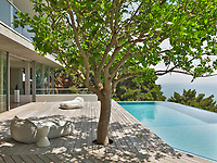 The contemporary home has a relaxed, peaceful quality with a seamless connection between indoor and outdoor living. The cantilevered terrace overlooks the pool and a tree provides a shady spot to sit and enjoy the view.