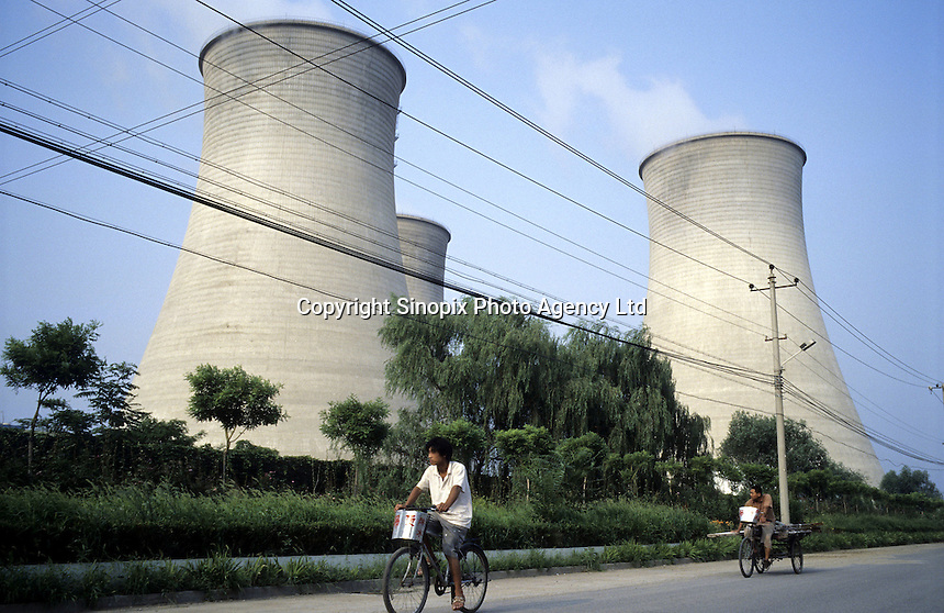 Bicycles pass the Beijing Huaneng Thermal Power Plant, China..