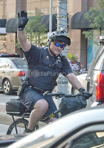 A police officer on a bicycle acknowledges the applause of bystanders as he and his colleagues ride down Euclid Avenue about two blocks from the Quicken Loans Arena, site of the 2016 Republican National Convention in Cleveland, Ohio on Saturday, July 16, 2016.<br /> Credit: Ron Sachs / CNP/MediaPunch<br /> (RESTRICTION: NO New York or New Jersey Newspapers or newspapers within a 75 mile radius of New York City)