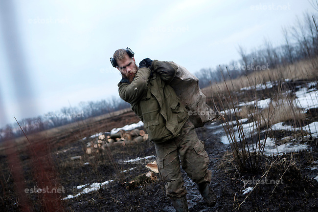 "UKRAINE, 02.2016, Oblast Donetsk. Ukrainian-Russian conflict concerning Eastern Ukraine / Foreign volunteers (""Task Force Pluto"") fighting with the far-right militia Pravyi Sektor against the Russian-backed separatists: Craig (USA) carries a bag full of wet firewood to their trench positions at the Donetsk frontline. © Timo Vogt/EST&OST"