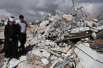 Palestinians inspect the rubble of a dairy factory demolished by Israeli bulldozers, at the al-Rama neighborhood near the West Bank city of Hebron on September 2, 2014. Israeli bulldozers demolished a dairy factory in Hebron and Bedouin homes east of Jerusalem early Tuesday. Photo by Mamoun Wazwaz