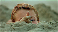 A young boy (model released) plays on the beach. Close up photo of boy pointing fingers as if he is firing a gun.  Photo taken on Sullivan's Island, near Charleston, South Carolina beach on the Atlantic Ocean, but could represent a beach scene anywhere.