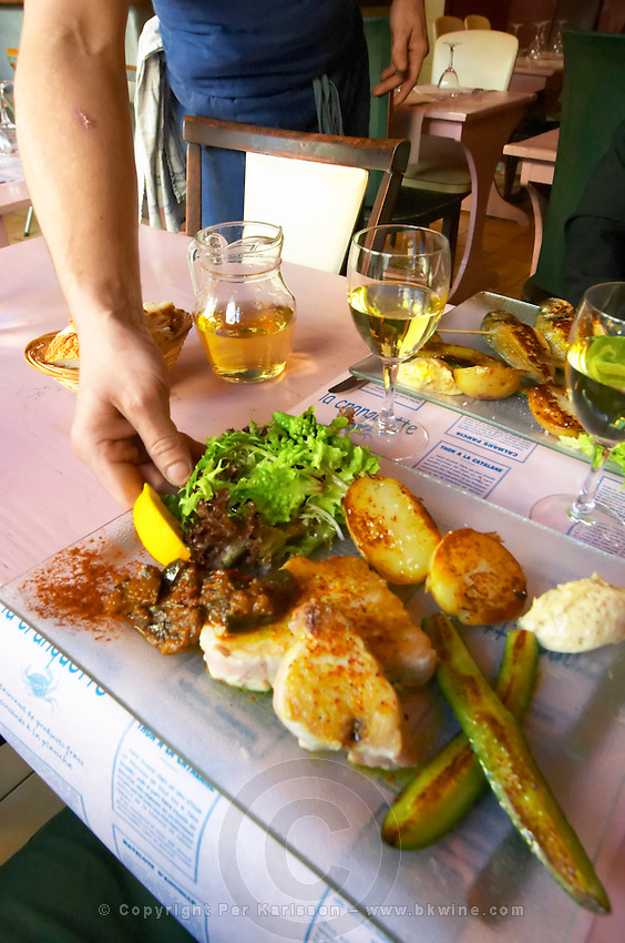 Gruissan village. La Clape. Languedoc. A waiter coming with the fish served for main course. Restaurant La Cranquette. Tuna fish with potatoes and salad. France. Europe.