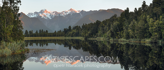 Perfect reflections of Southern Alps in Lake Matheson at sunset, Westland Tai Poutini National Park, West Coast, UNESCO World Heritage Area, New Zealand, NZ