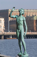 In the Garden of Stadshuset, the Stockholm Town Hall. a bronze statue Song by Carl Eldh a naked man holding a bunch of grapes. In the background the royal palace Stockholm, Sweden, Sverige, Europe