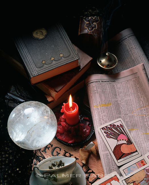 Crystal ball, ouija board, tarot cards, tea leaves and stock market page in newspaper