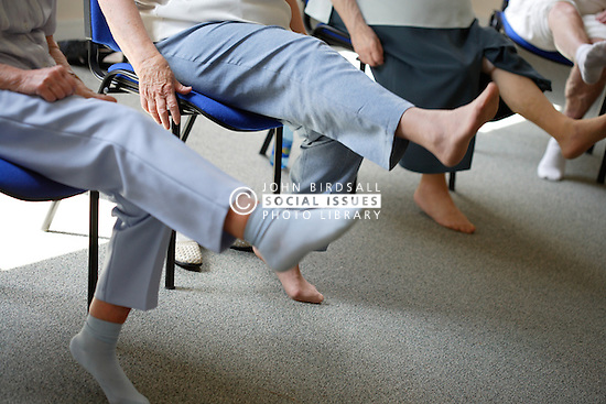 Group of older women doing leg stretching exercises at a keep fit class,