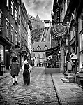 Two people in medieval costumes walking up the Rue Sous Le Fort street in old Quebec City with funicular in the background. Black and white photo. Souvenirs du Lys, Sous le Fort, La Chasse-Galerie boutique and other shops and restaurants. Quebec, Canada. Rue Sous-Le-Fort, Ville de Québec.