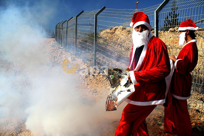 Palestinian demonstrators dressed as Santa Claus take part in the weekly protest against Israel's separation barrier in the West Bank village of Bilin near Ramallah on December 24, 2010. Photo by STR