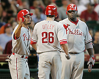 Phillies Shane Victorino and Ryan Howard greet Chase Utley after he homered against the Astros on Sunday May 25th at Minute Maid Park in Houston, Texas. Photo by Andrew Woolley / Four Seam Images.