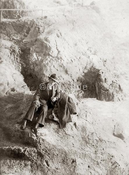 Old photo of a Japanese man sitting on sandy rocks.