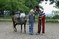 Shetland-Pony, Shetlandpony, Shetty, Shetti, Ponyhof, Shetland - Pony wird eingeritten, zunächst Führung am Halfter mit Reitlehrerin und Kind, Reiten