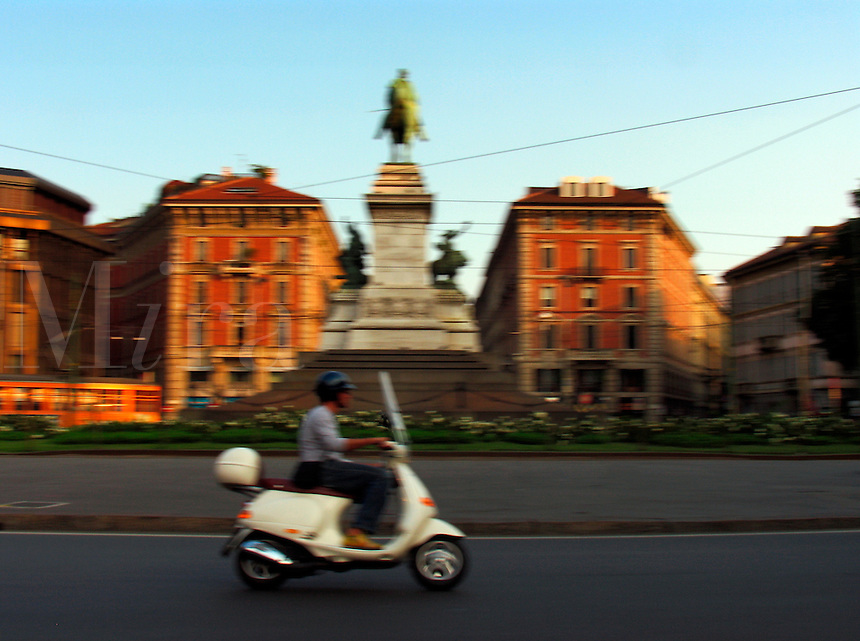 Fast moving ET4 Vespa scooter in traffic circle with Garibaldi monument, Milan, Ital