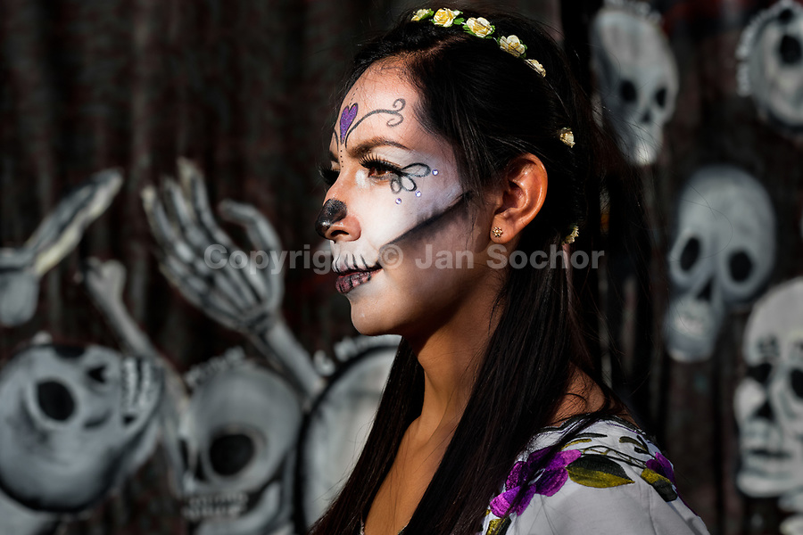 A young woman, dressed as La Catrina, a Mexican pop culture icon representing the Death, walks through the town during the Day of the Dead celebrations in Mexico City, Mexico, 28 October 2016. Day of the Dead (Día de Muertos), a syncretic religious holiday combining the death veneration rituals of the ancient Aztec culture with the Catholic practice, is celebrated throughout all Mexico. Based on the belief that the souls of the departed may come back to this world on that day, people gather at the gravesites in cemeteries praying, drinking and playing music, to joyfully remember friends or family members who have died and to support their souls on the spiritual journey.