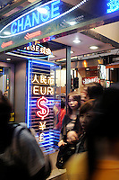 People walk pass a currency exchange shop in Hong Kong. Hong Kong is a tax-free shopping paradise with hundreds of money exchange centres..