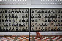A visitor looks at pictures of victims of Khmer Rouge regime at the former notorious Tuol Sleng prison that is now the Genocide Museum in Phnom Penh August 5, 2014. Cambodia's young population is very aware of its grim history, with almost every family suffering losses. Most Cambodians still want justice and to see the U.N.-backed court find the recalcitrant Nuon Chea, Pol Pot's right-hand man, and ex-President Khieu Samphan, guilty of crimes against humanity, but the court has been mired in disputes, resignations, funding shortages and accusations of political interference and has to date delivered just one verdict. The court will deliver verdicts for Noun Chea and Khieu Samphan on August 7, 2014. Picture taken August 5, 2014. REUTERS/Damir Sagolj (CAMBODIA)
