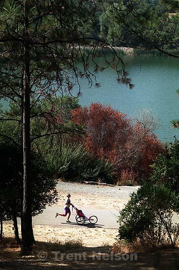 Woman jogging with baby runner stroller around Lafayette Reservoir<br />