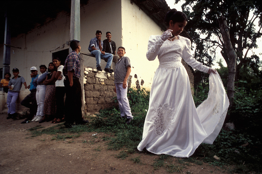 The incoming Queen of the Flowers examines her dress outside a ballroom in Tatumbla, Honduras.