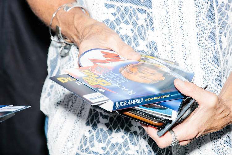 A woman holds campaign materials while waiting to meet Republican presidential candidate Dr. Ben Carson at Londonderry Old Home Day in Londonderry, New Hampshire.