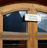 "A sign reading ""gone skiing' hangs on the front door of a chalet"