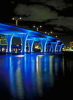 highway bridge illuminated in blue light leading to shipping port in Miami. Miami Florida USA.