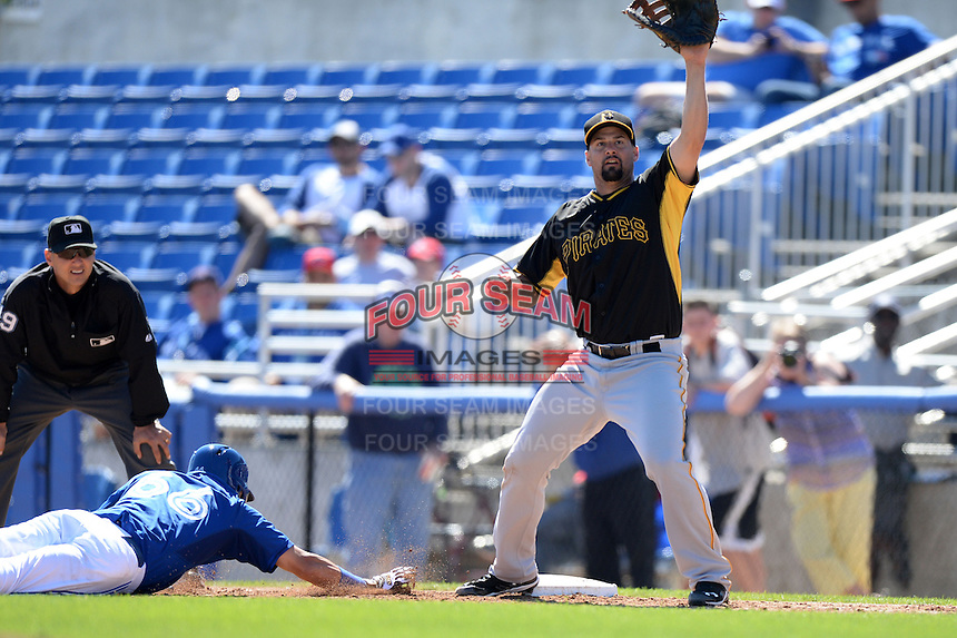 First baseman Gaby Sanchez (17) of the Pittsburgh Pirates stretches for a throw as Munenori Kawasaki (66) dives back to the bag during a spring training game against the Toronto Blue Jays on February 28, 2014 at Florida Auto Exchange Stadium in Dunedin, Florida.  Toronto defeated Pittsburgh 4-2.  (Mike Janes/Four Seam Images)